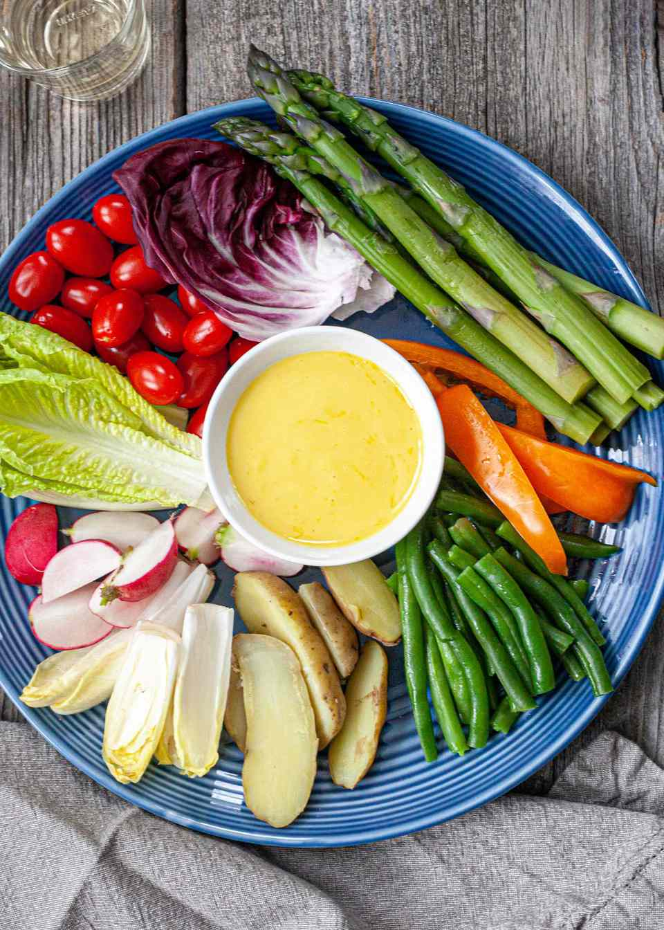 A plate with homemade aioli in a small bowl in the center of a plate. The aioli sauce is surrounded by a variety of steamed and fresh vegetables.