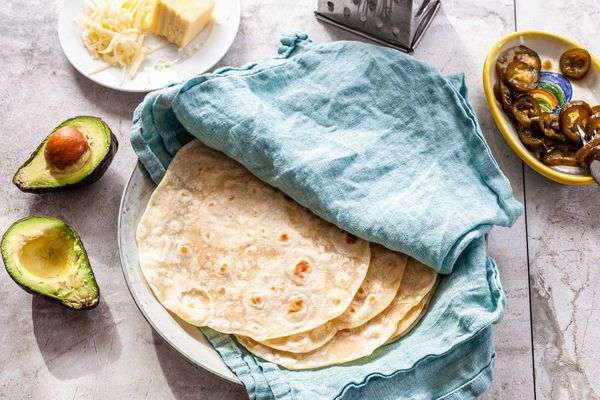 Homemade flour tortillas on a plate in-between a teal linen. A small bowl of pickled jalepanos, a box shredder, shredded sheese and a halved avocado are around the plate.