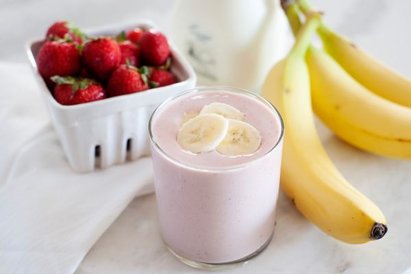 Quick and easy strawberry banana smoothie garnished with sliced bananas and with whole fruit set around it.