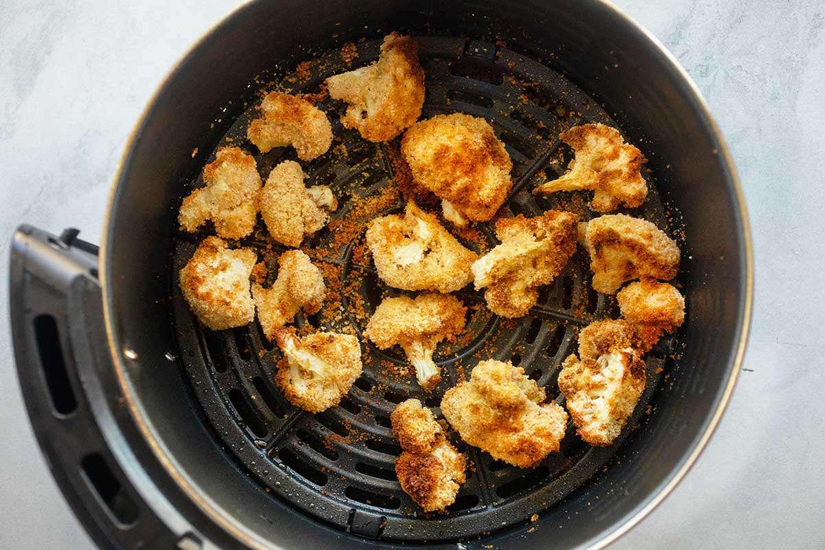 Golden air fried cauliflower florets inside a black air fryer.