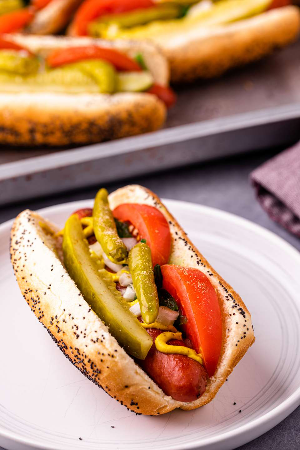 Chicago-style hot dog on a plate with more hot dogs in buns behind it on a baking sheet.