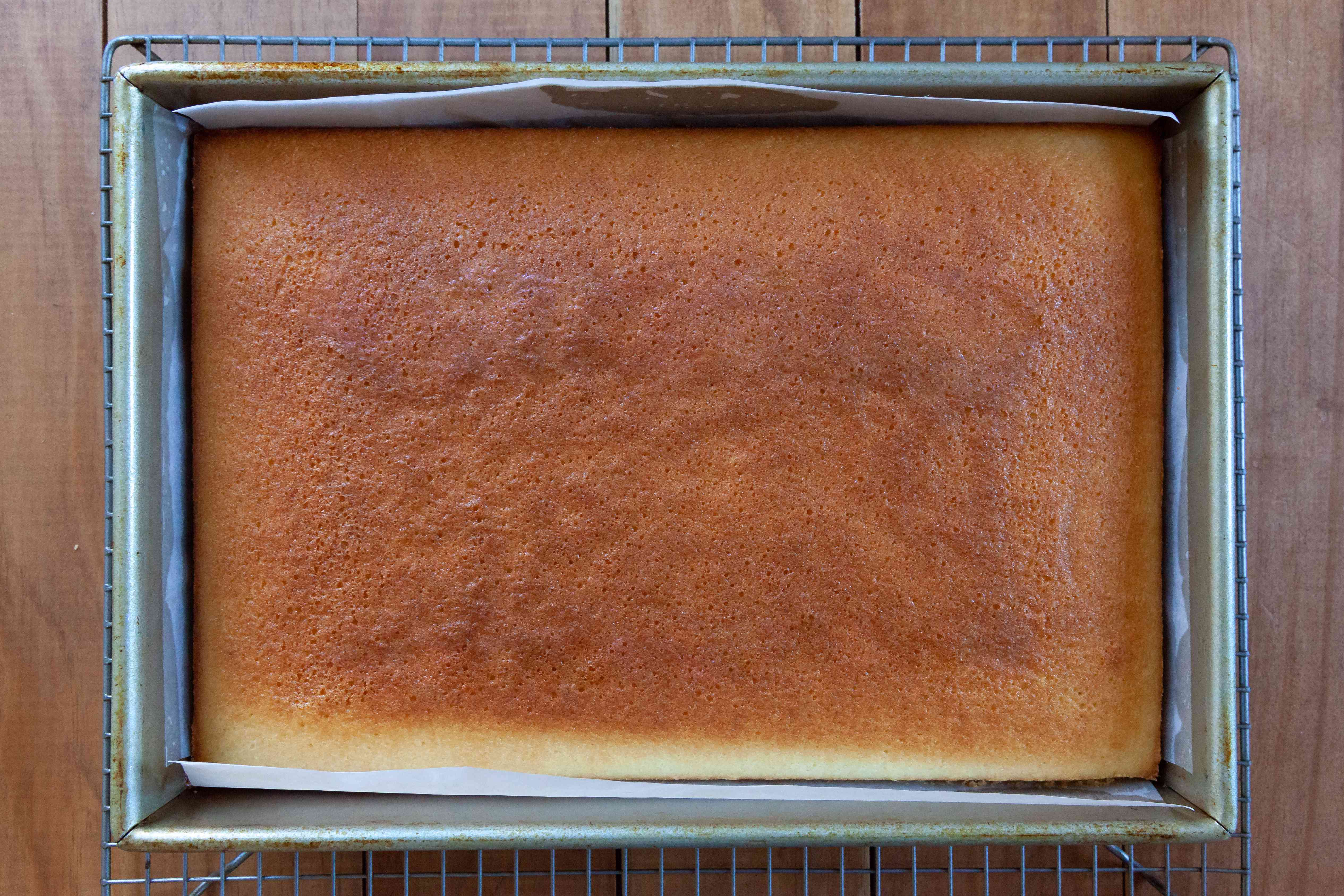 An easy white cake cooling on a rack.