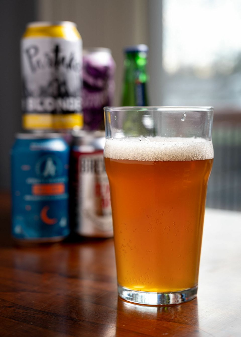 A glass of beer with cans of non-alcoholic beers stacked behind it.