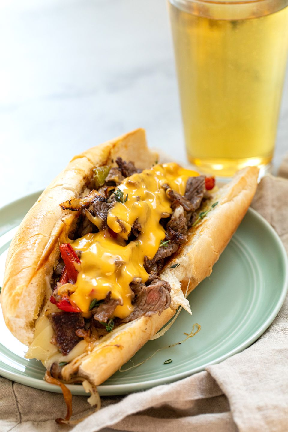Homemade Philly Cheesesteak on a plate with a tall beer behind it.