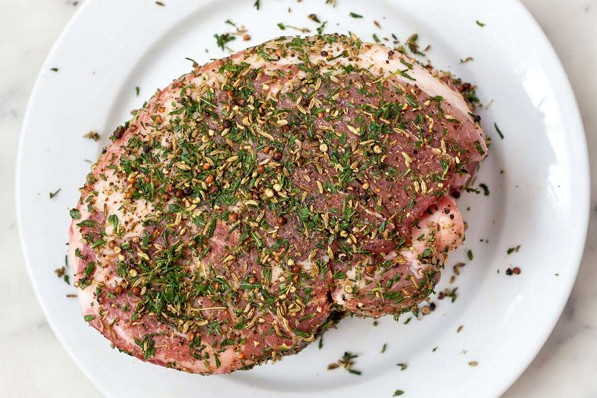 Pork roast recipe for oven with herbs and spices sprinkled over the top.