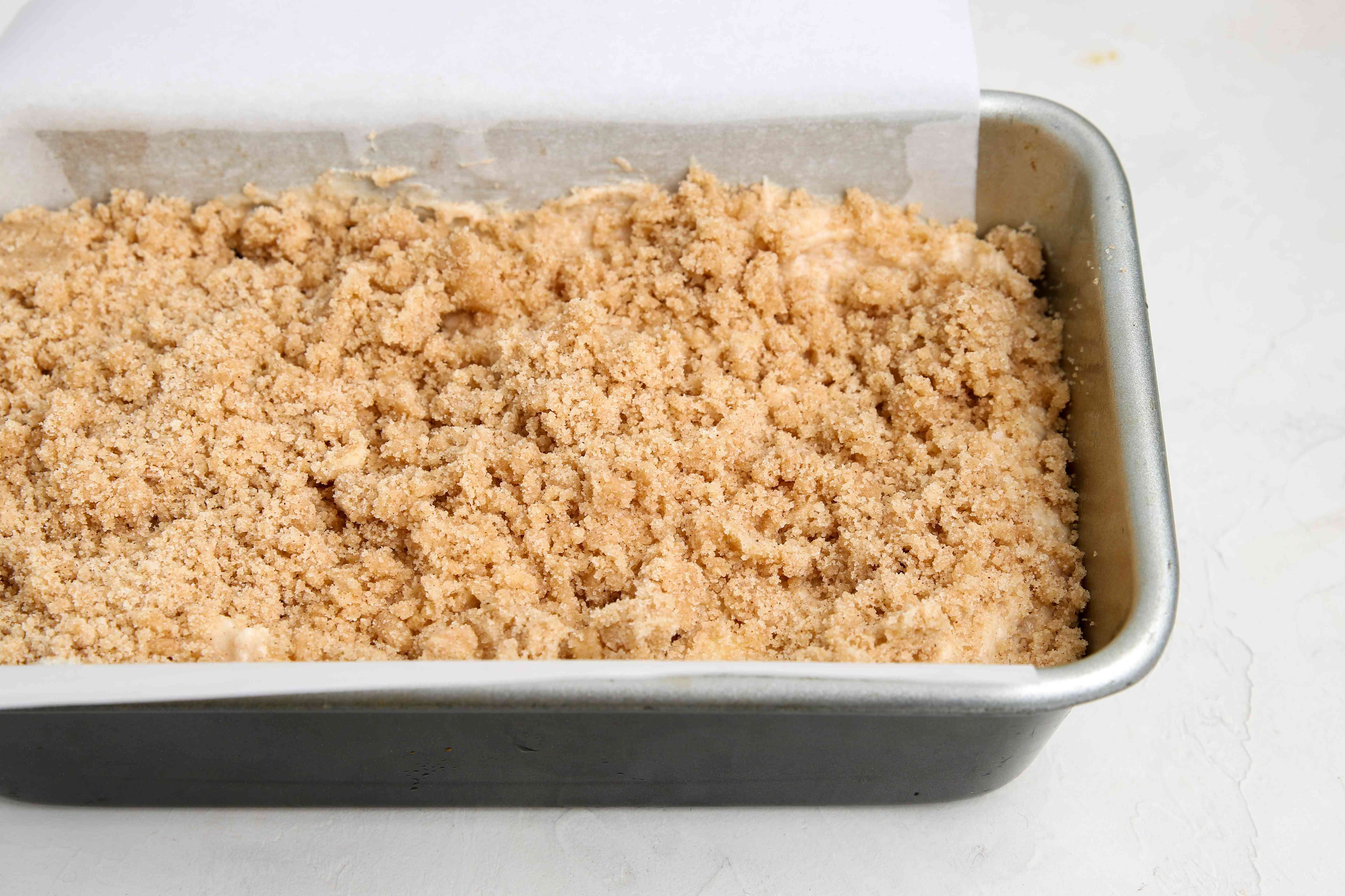 Loaf pan with cinnamon streusel apple bread ready to be baked.