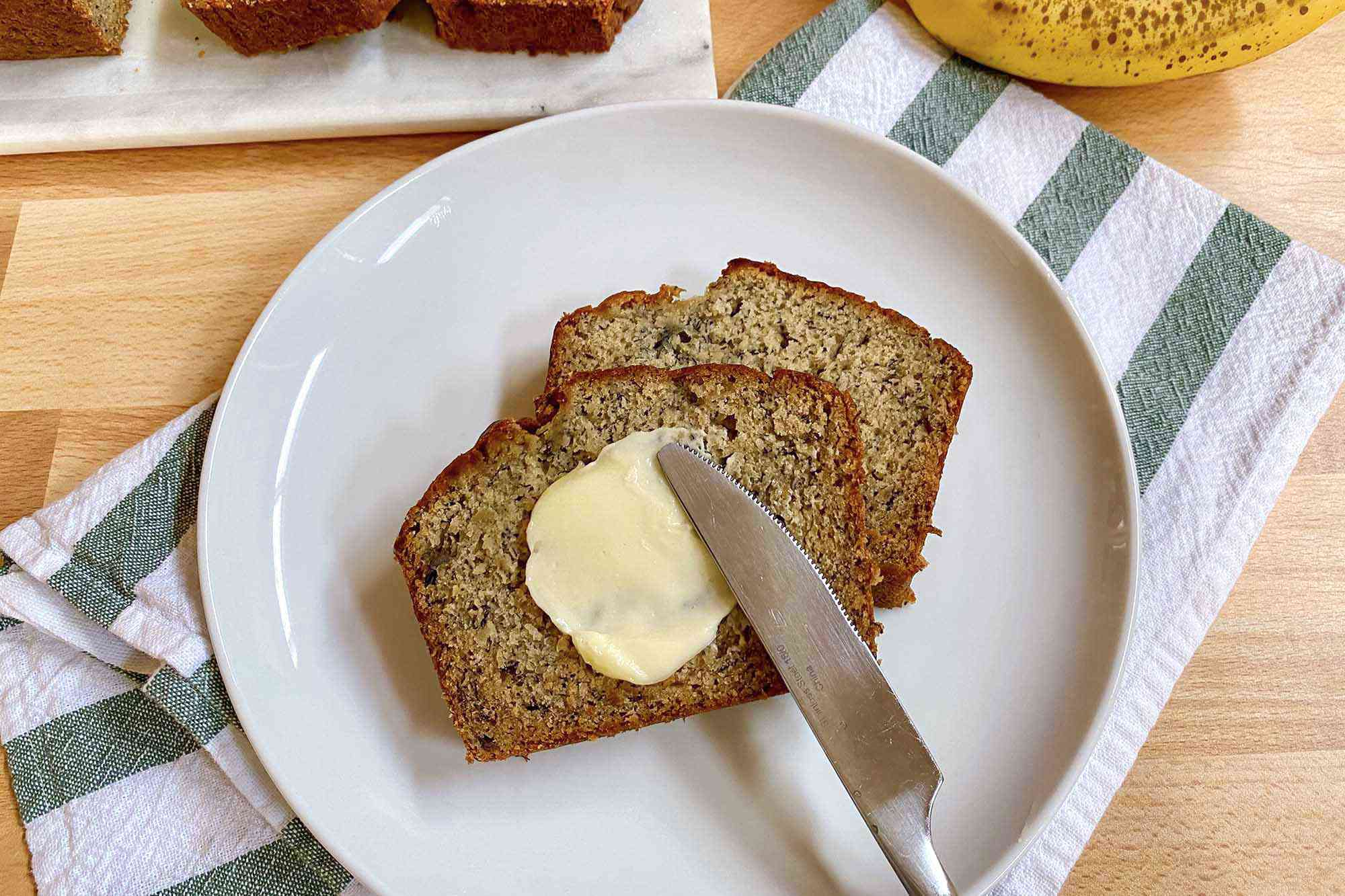 Two slices of easy gluten free banana bread with a pat of butter being spread on top.