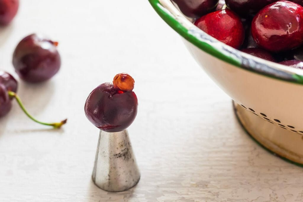 How to pit cherries with a metal pastry tip with a cherry on top with the pit popped out. A bowl of cherries are in partial view to the right.