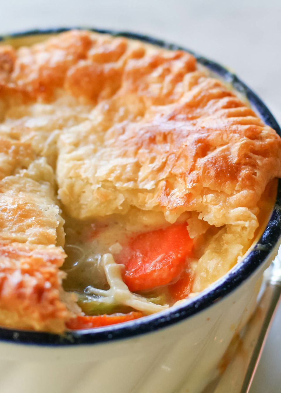 A chicken pot pie with a golden crust and creamy filling is in a ramekin.