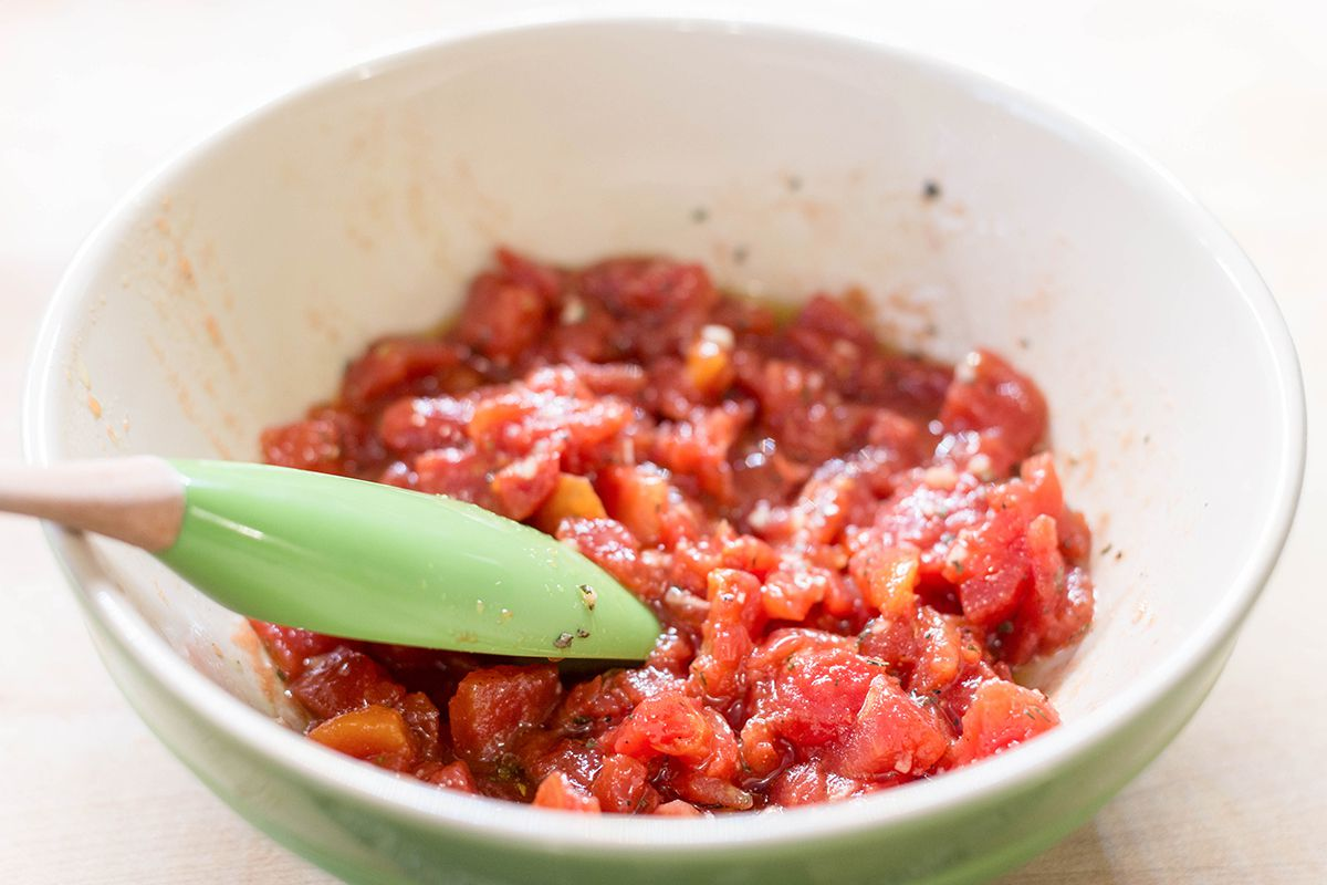 Mix together the tomato topping for Cheesy Bruschetta Chicken Cutlets