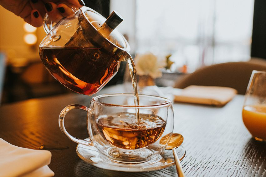 Hand pouring a cup of tea from a stylish transparent teapot into a clear cup