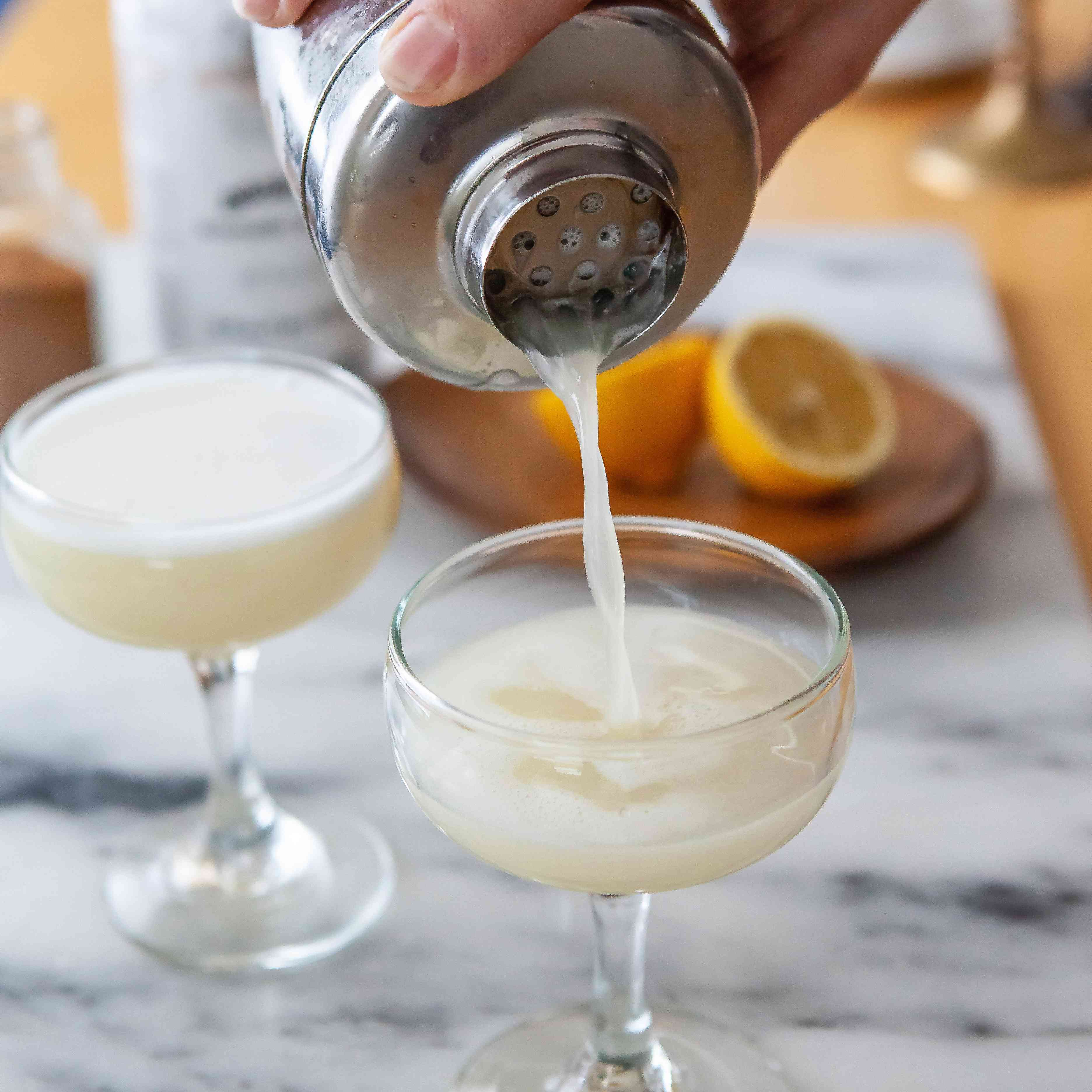 An Authentic Peruvian Pisco Sour being poured into a coupe glass.