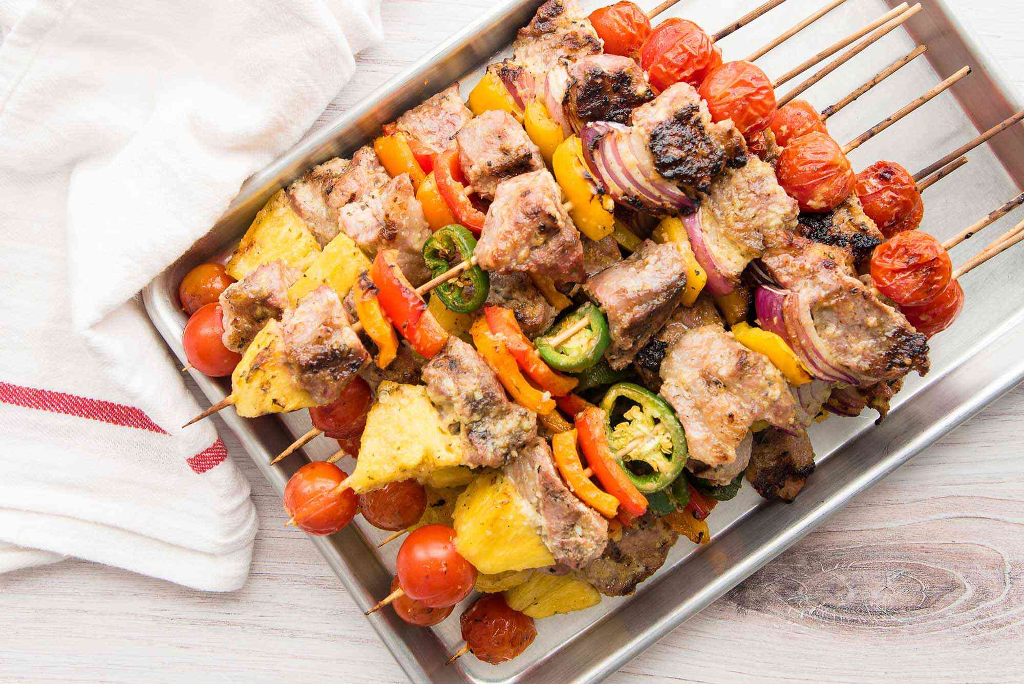 A quarter sheet pan has pork kebabs with grilled pineapple stacked on it.