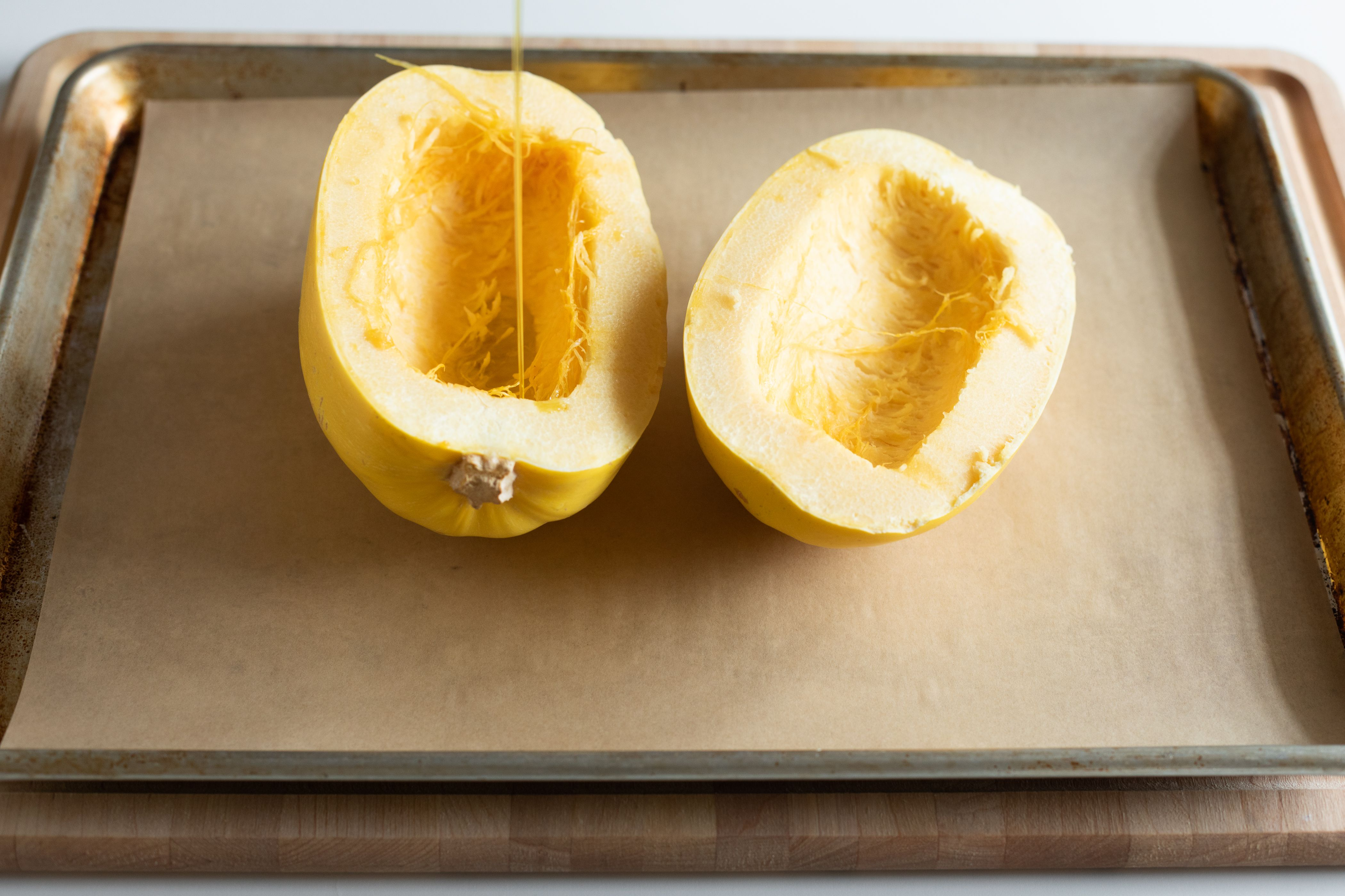 Pouring olive oil and salt on halved spaghetti squash