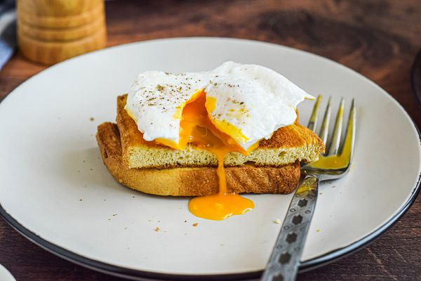 Side view of a poached egg on halved toast with the yolk running over the side.