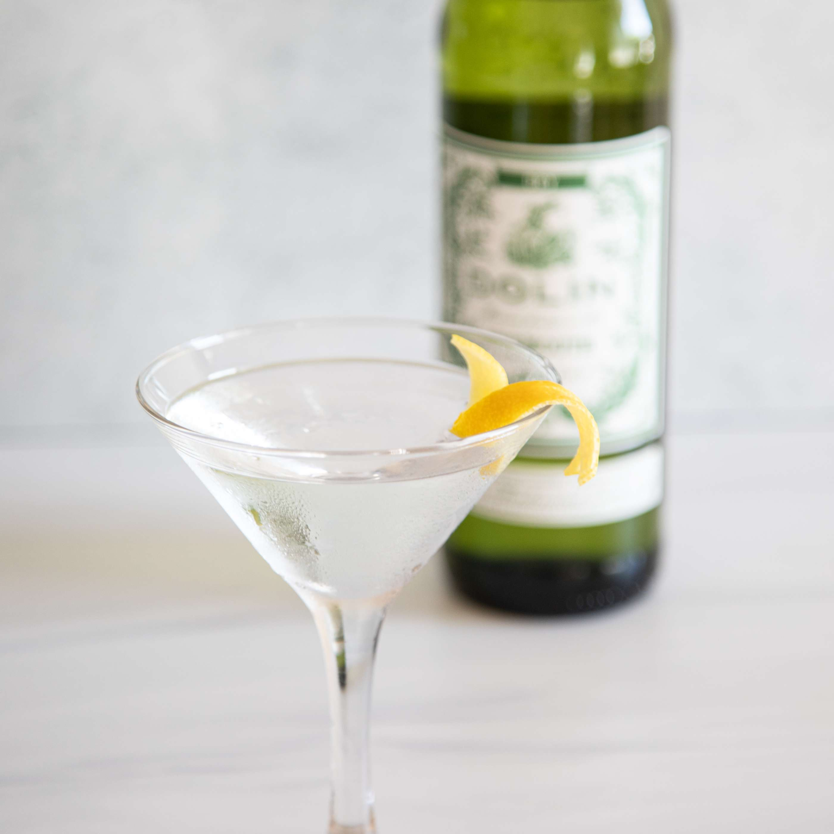 50/50 Vodka Martini with a lemon peel garnish and a bottle in the background.