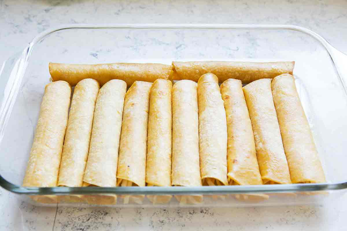 fill enchilada casserole dish with rolled tortillas