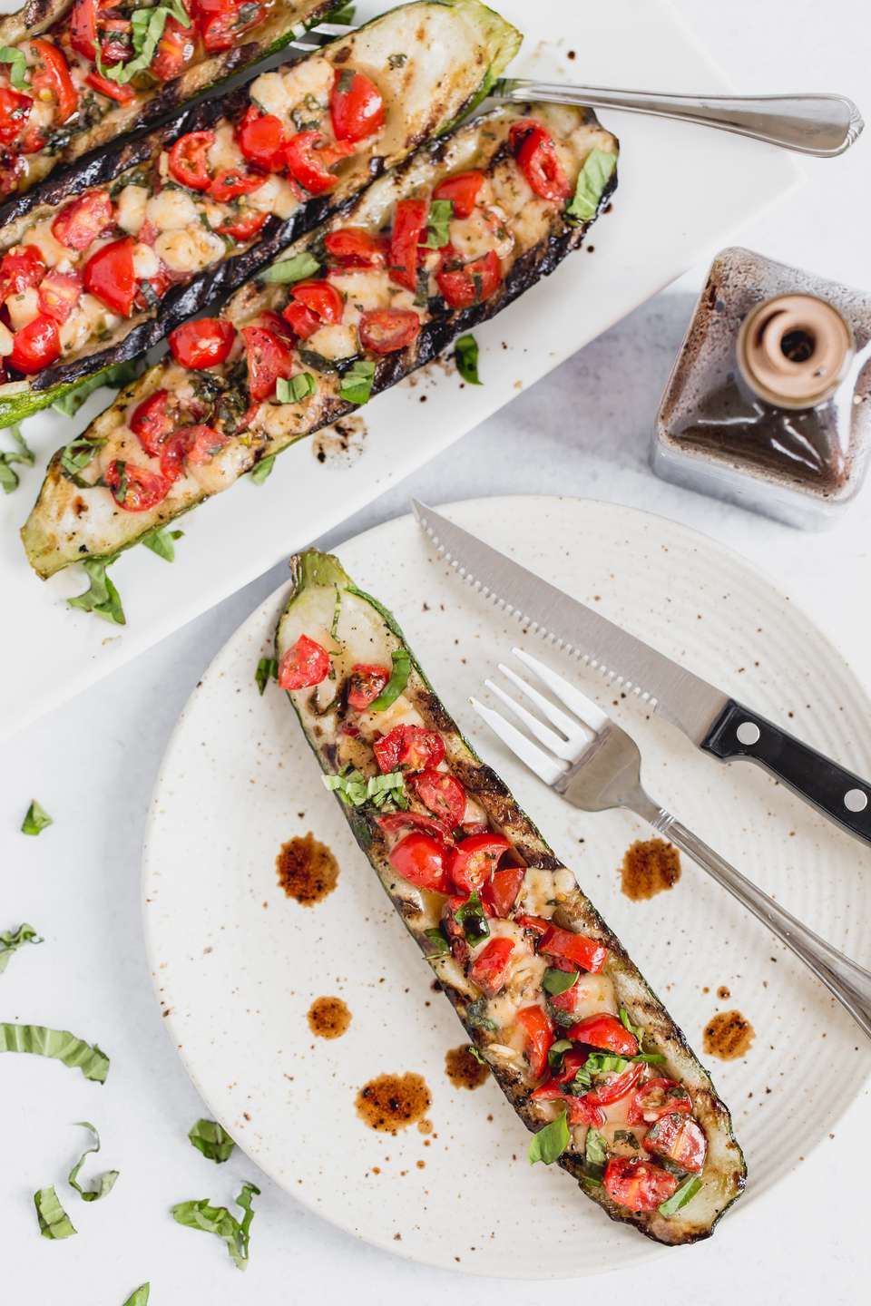 A plate with a grilled zucchini boat with caprese stuffing and additional boats behind it.
