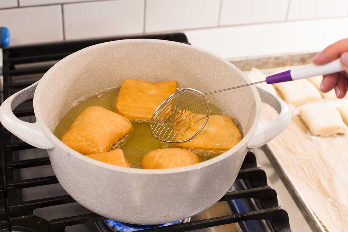 New Orleans Beignets are in a dutch oven on the stove being turned in the hot oil. One side is golden brown. A slotted spoon is being used to turn them.