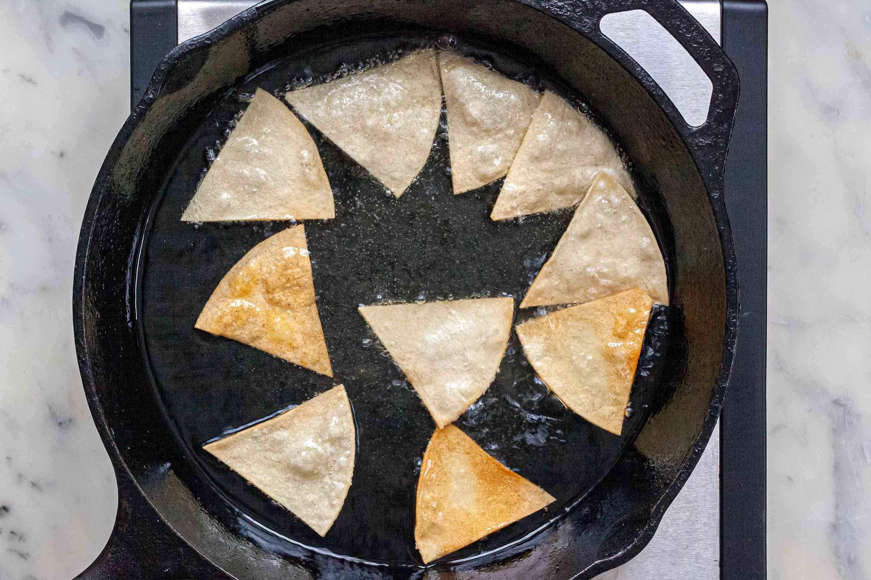Frying tortillas for homemade tortilla chips.
