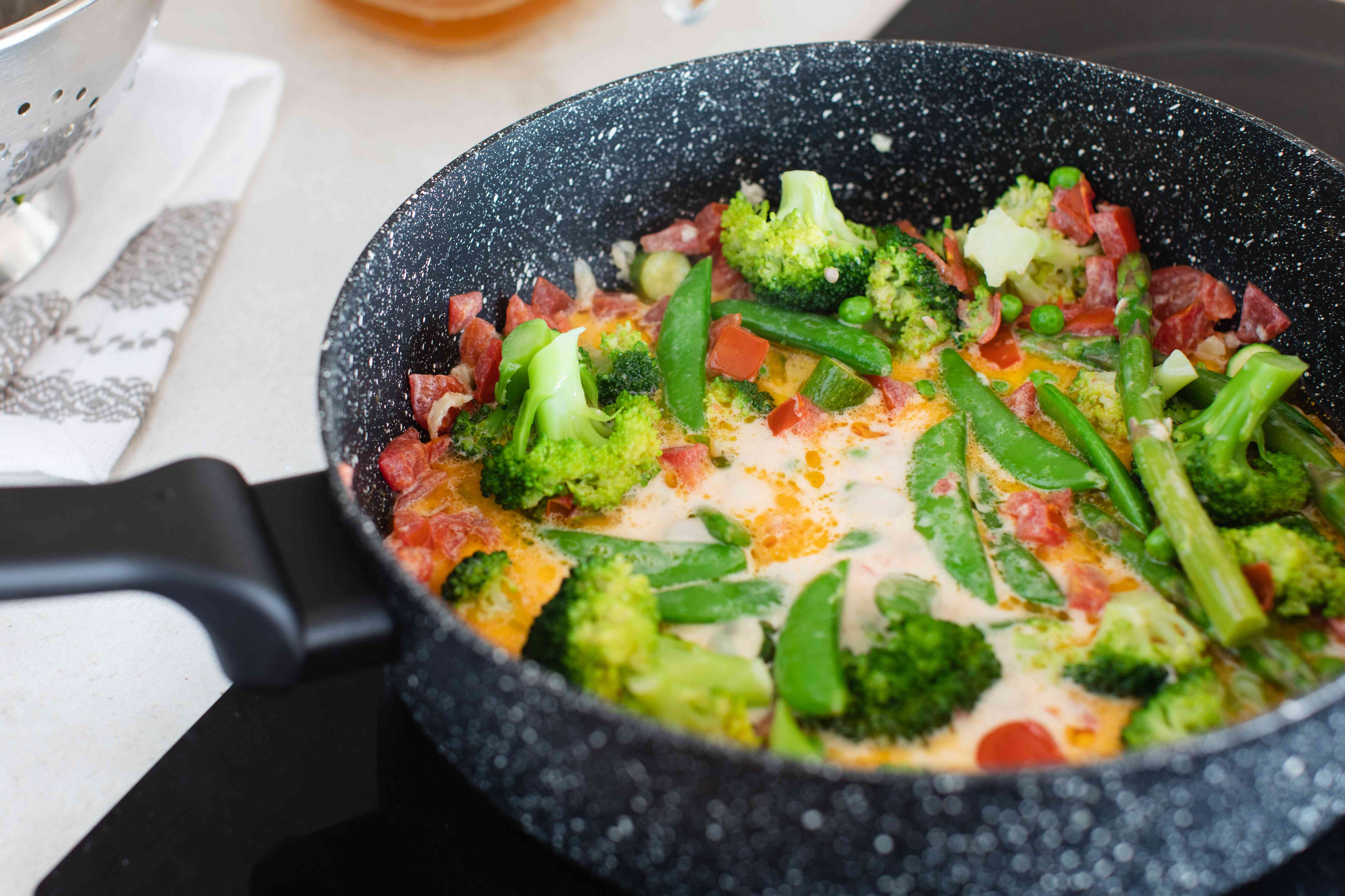 A skillet with the vegetables and primavera sauce inside.