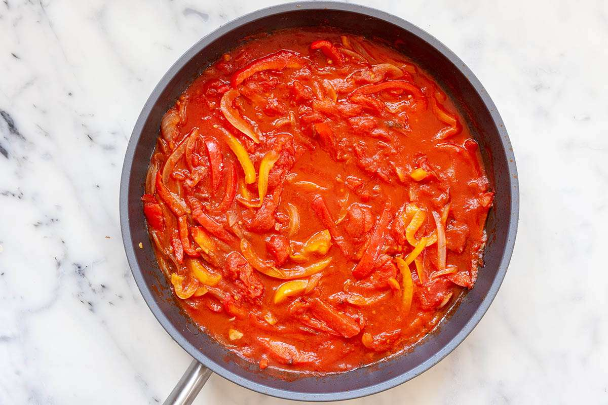 A skillet of sliced peppers in tomato sauce to make a Healthy Egg and Vegetable Skillet Breakfast.