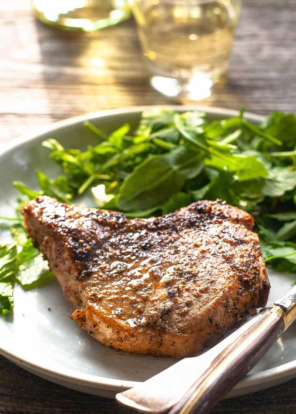 Easy Pork Chop Recipe pork chop on plate with greens