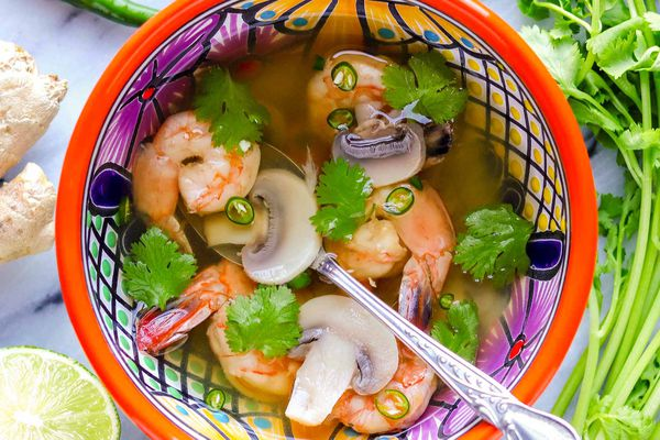 Thai soup with shrimp in a brightly patterned bowl with a silver spoon inside. Sliced lime, ginger, peppers and cilantro stems suround the bowl of light broth, shrimp, mushrooms and cilantro.