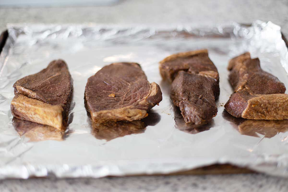 Four balsamic marinated steaks on foil on a baking sheet.