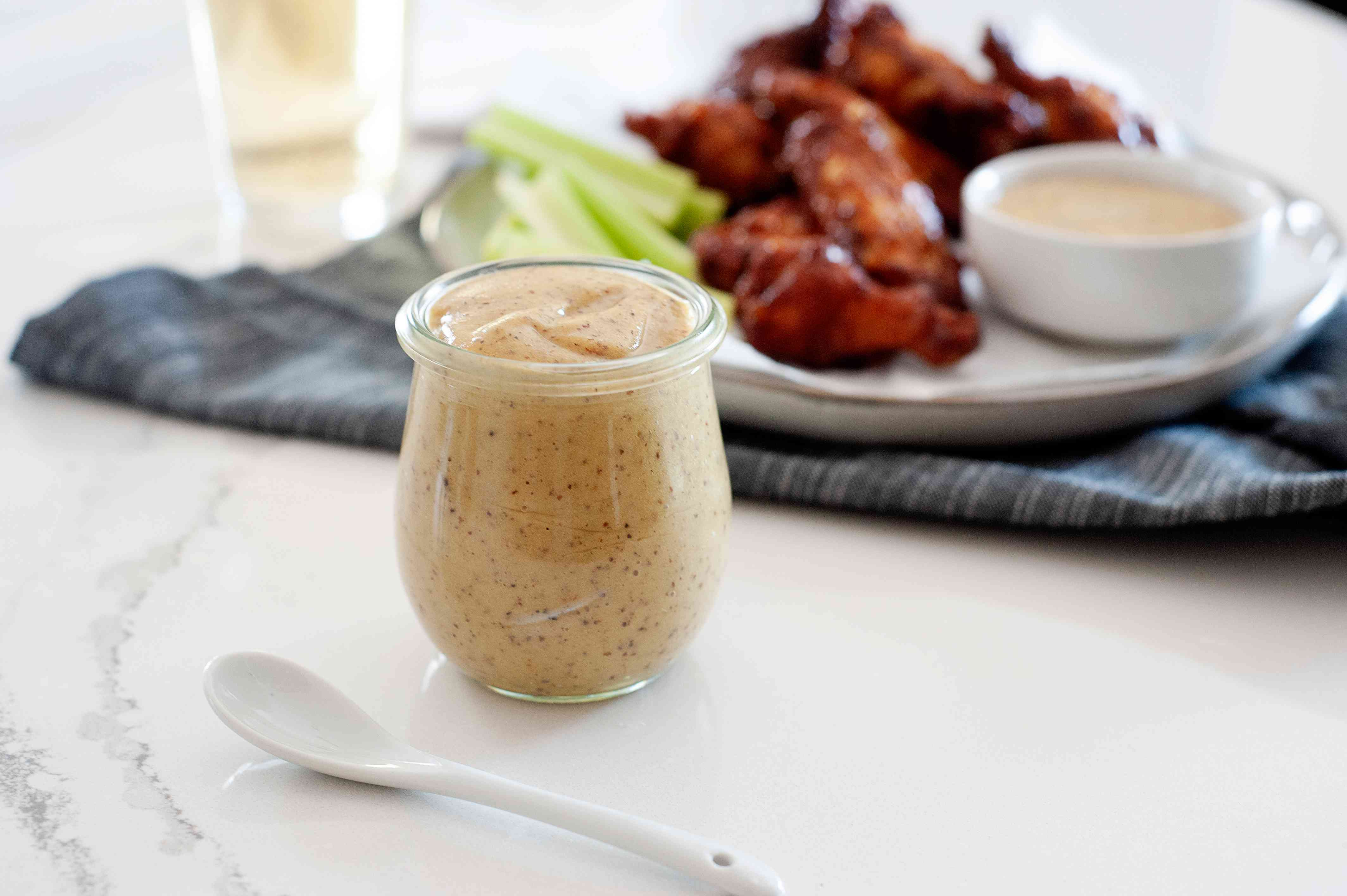 Side view of homemade honey mustard in a glass jar with a plate of chicken wings behind it.