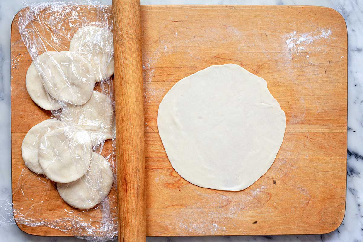 Small disks of dough to make flour tortillas are on a wooden cutting board. A rolled out tortilla is to the right on the cutting board and a rolling pin separates the disks from the finished tortilla.