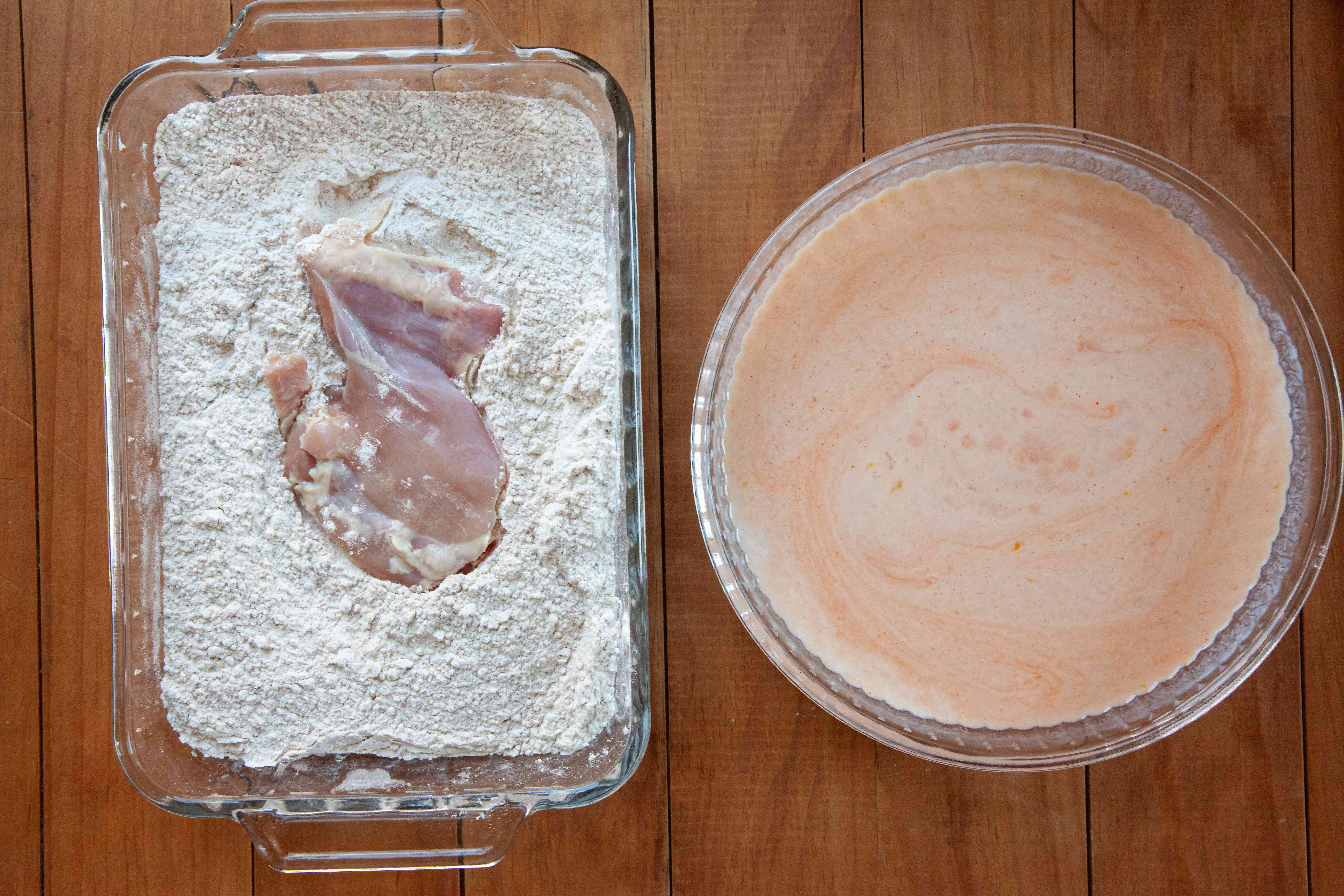 Chicken thighs being coated in flour mixture for a Nashville-style hot fried chicken.