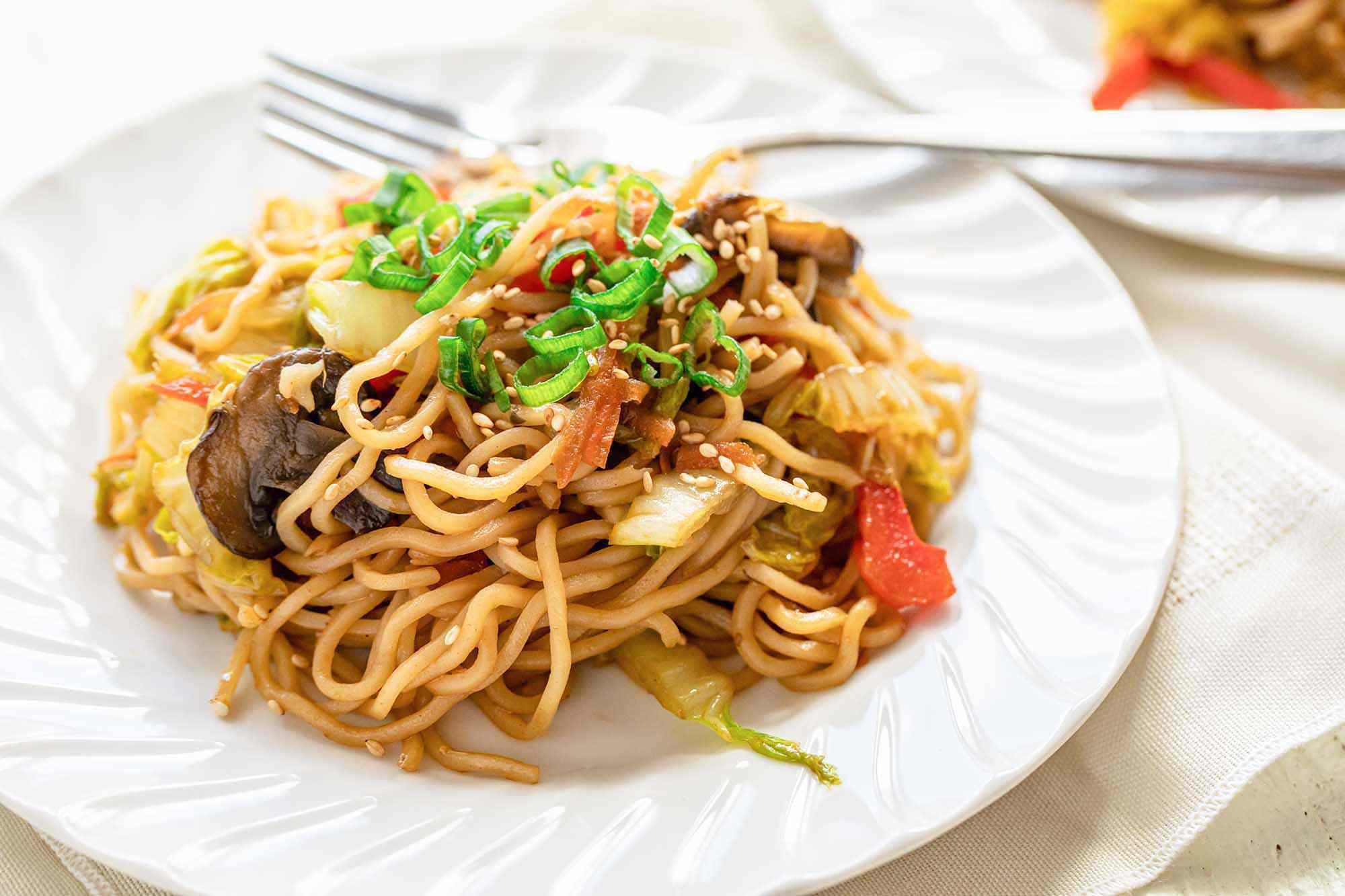 Side view of a white plate and fork with homemade vegetable lo mein. A fork is on the plate and a second plate is partially visible in the upper right hand corner.