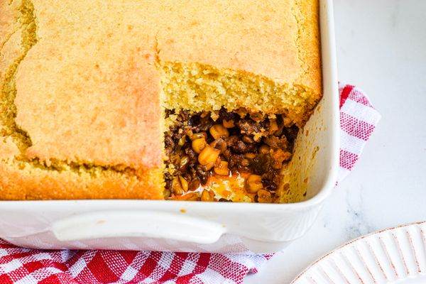 A casserole dish with a tamale pie and a piece missing.