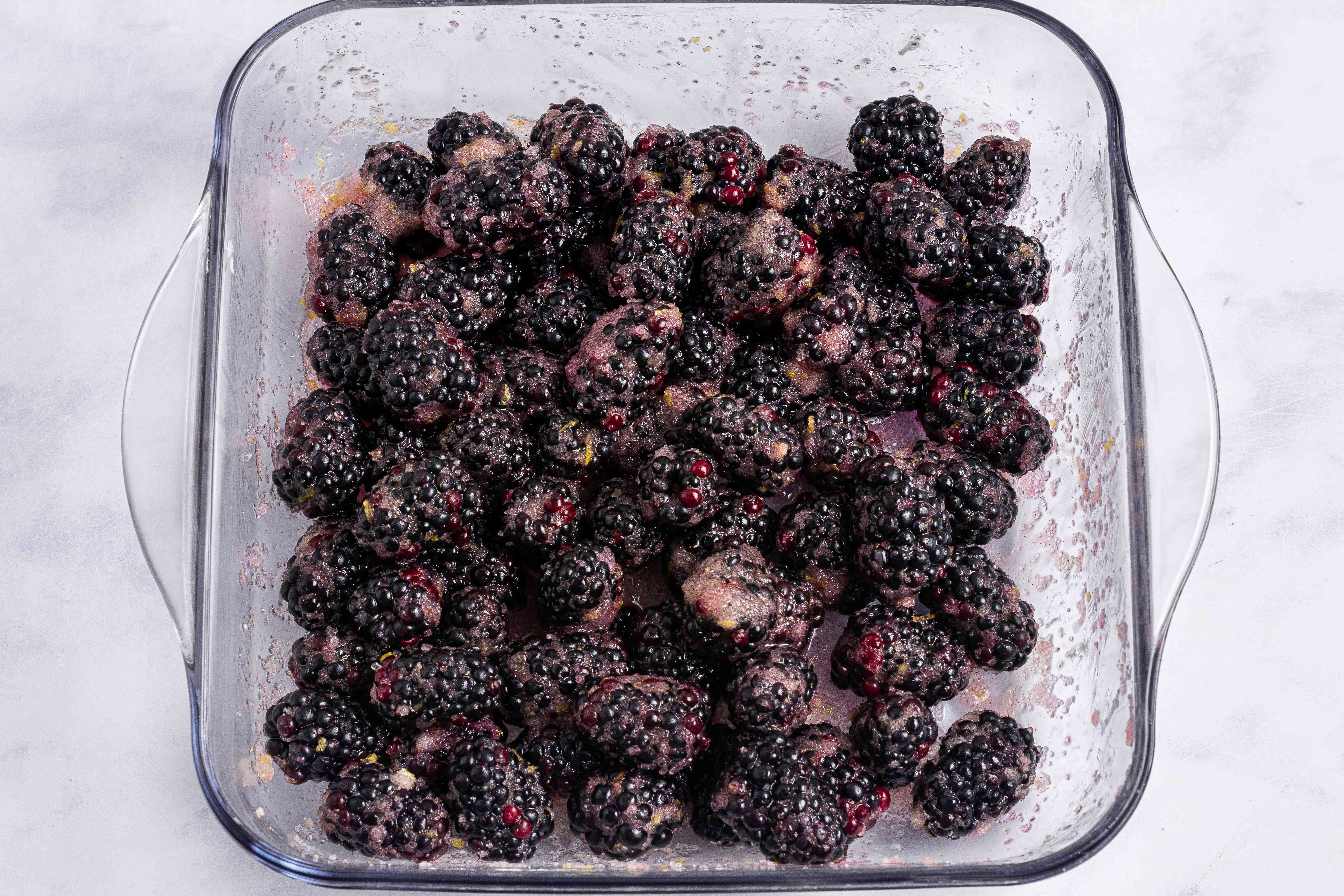 Overhead view of of a baking dish with blackberries in the bottom to make a blackberry cobbler recipe.