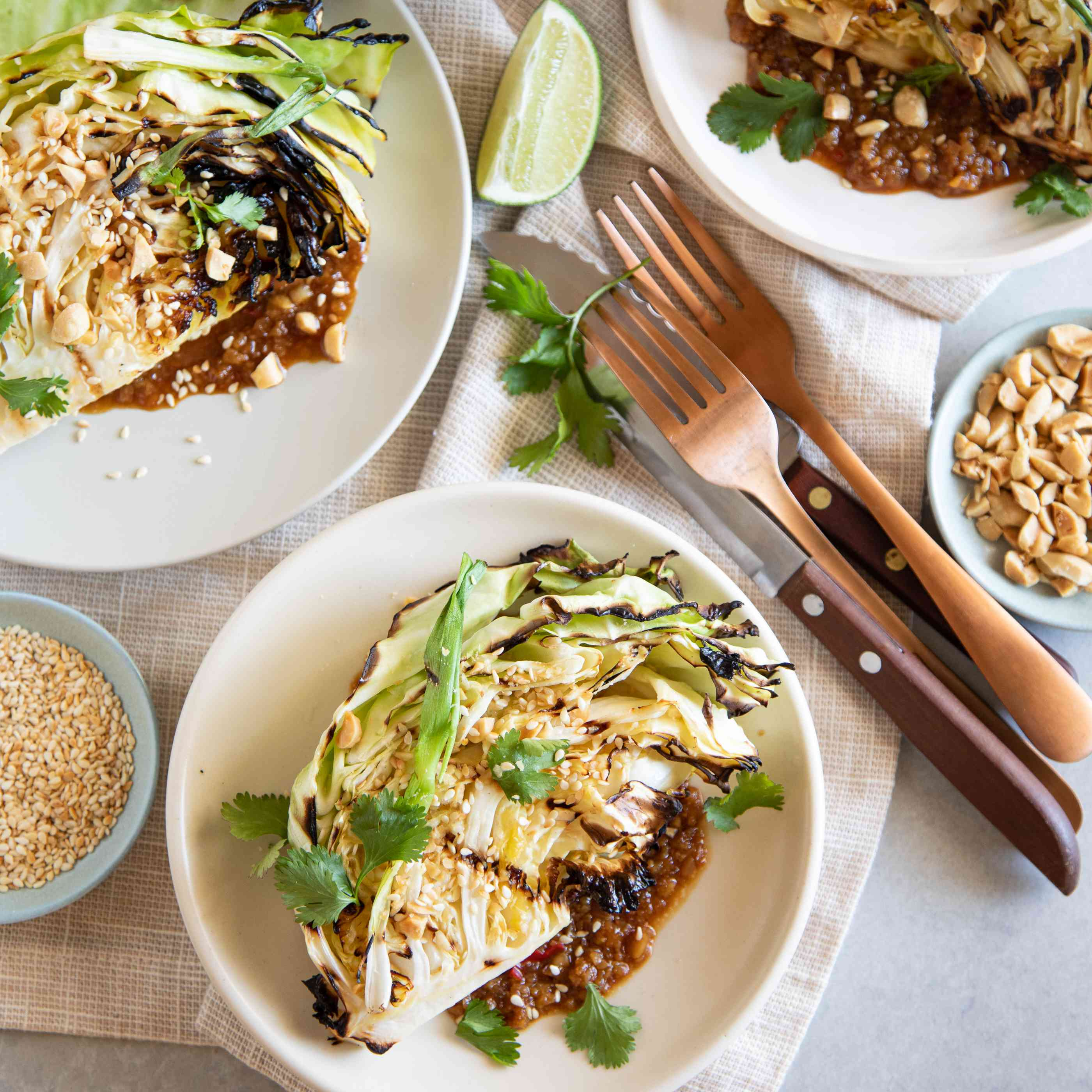 Grilled cabbage wedges with peanut sauce on a plate with utensils and toppings set around it.