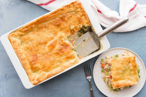 Homemade Chicken Pot Pie with a golden crust has a serving removed and set on a white plate to the right.