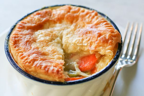 A pot pie with a golden crust is in a ramekin with some of the crust removed to show the filling.