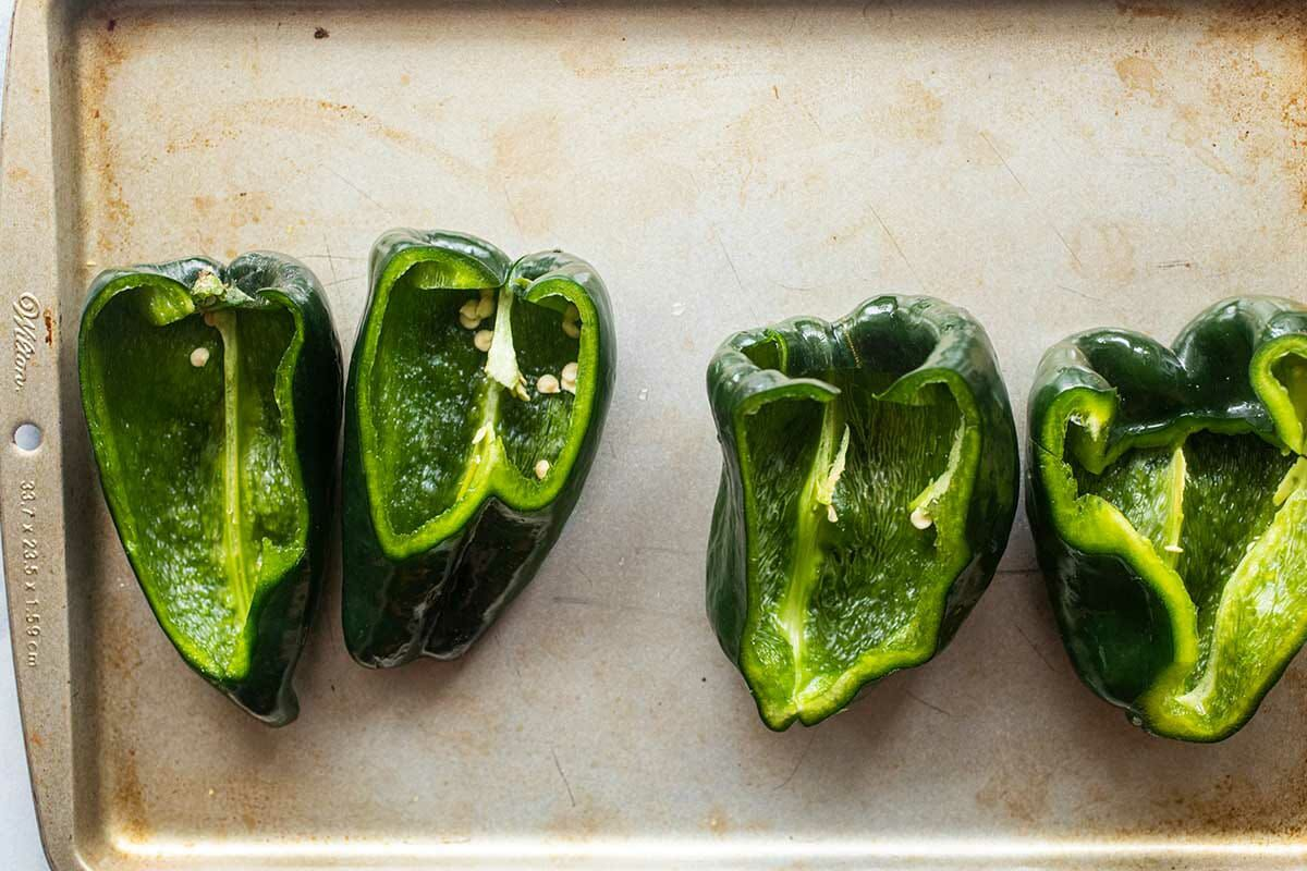 Seeded poblano peppers on a baking sheet with the top part cut off to show how to make stuffed peppers.