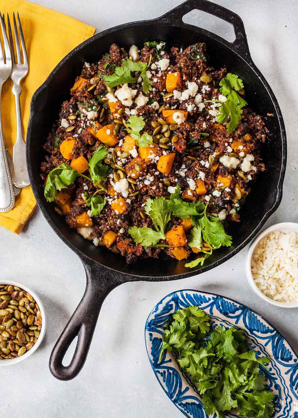 Top view of a cast iron skillet of vegetarian skillet dinner with pumpkin seeds, quinoa, butternut squash and cilantro visible in the pot. Clockwise around the pot is a small bowl of white rice, a small platter of cilantro, a ramiken of roasted pumpkin seeds and a yellow napkin with two forks side by side.