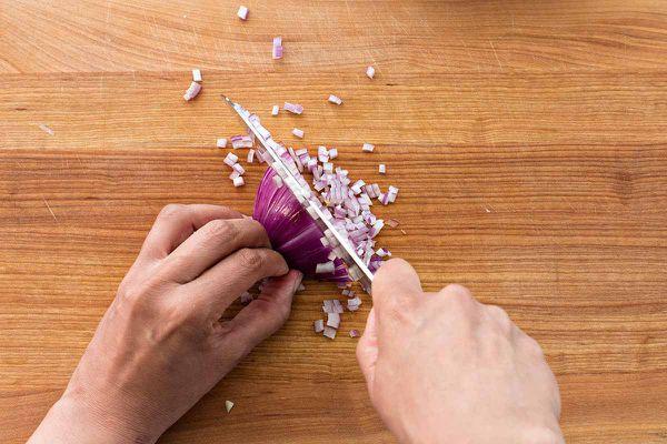 Copycat Guacamole Recipe - person mincing an onion