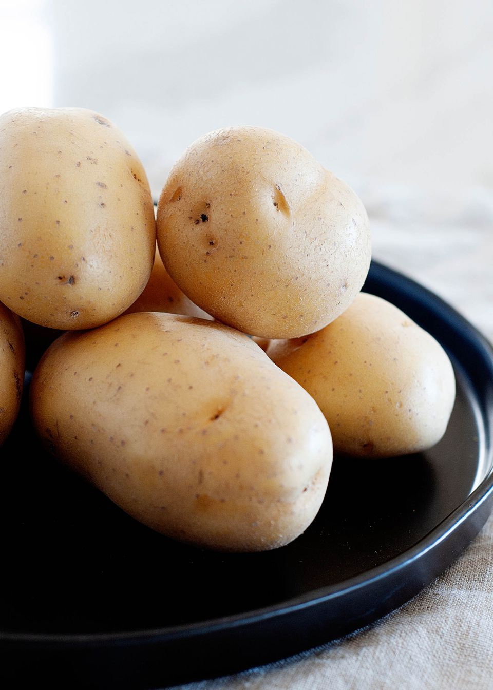 Side view of yellow potatoes on a black tray.