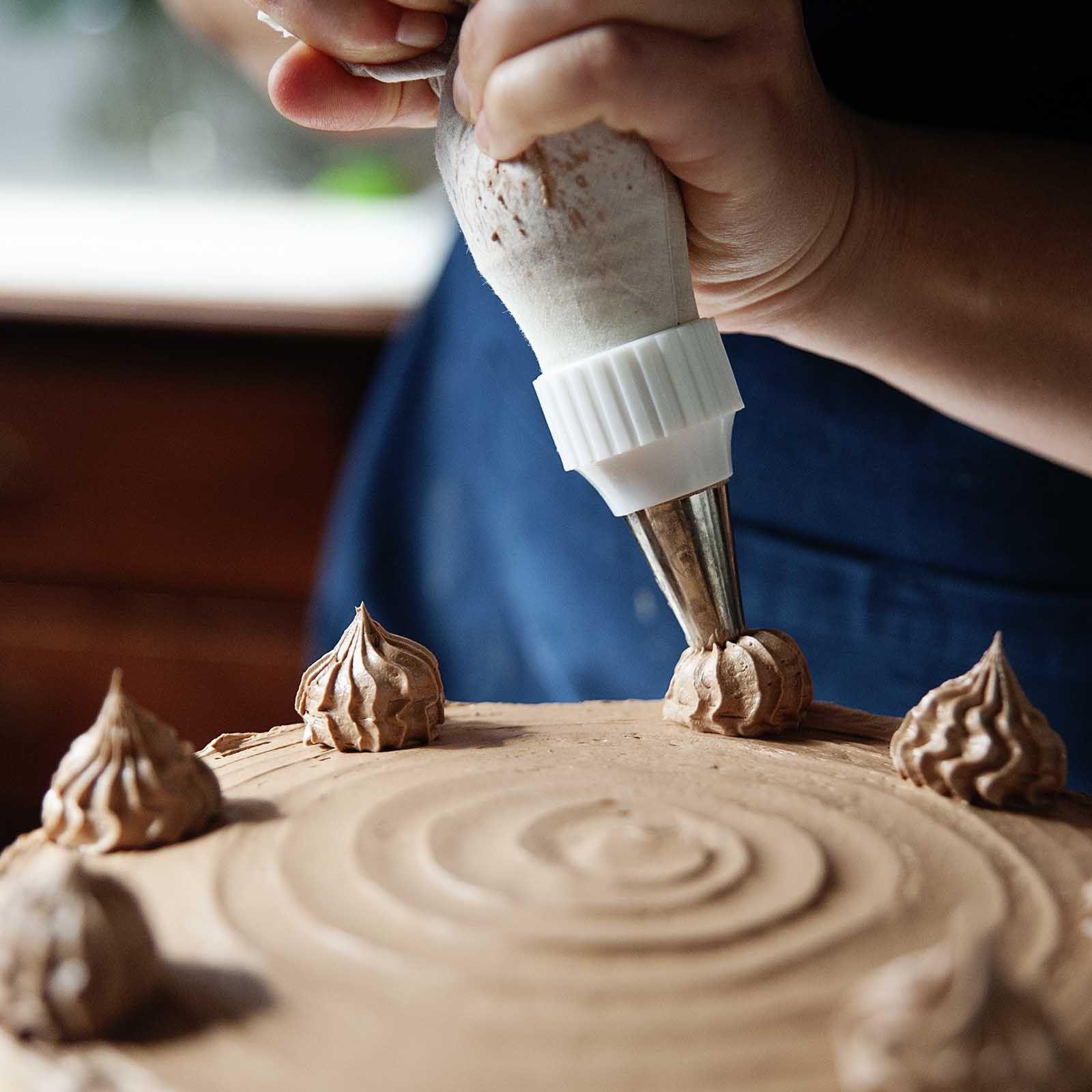 Woman piping Chocolate Swiss Meringue Buttercream on a chocolate layer cake.