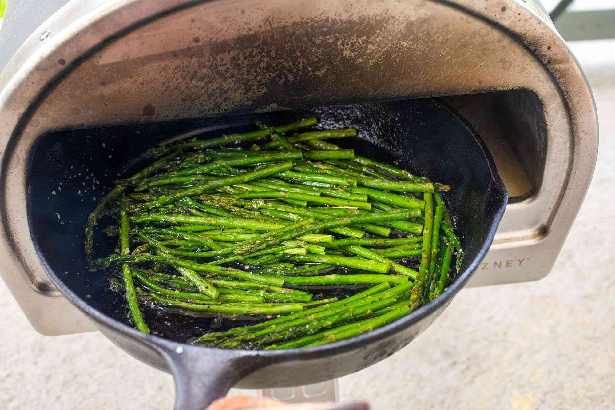 Roccbox pizza oven with a cast iron skillet of asparagus being pulled out of it.