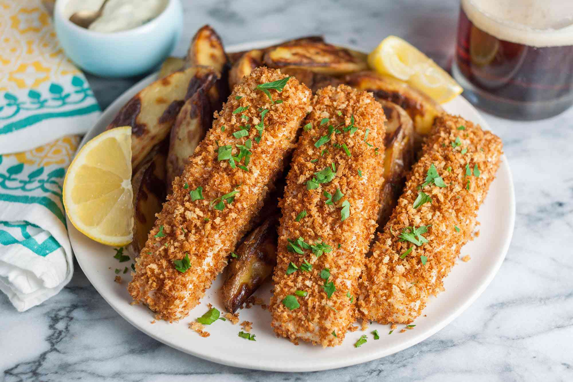 Breaded Fish and Chips on plate with lemon wedge