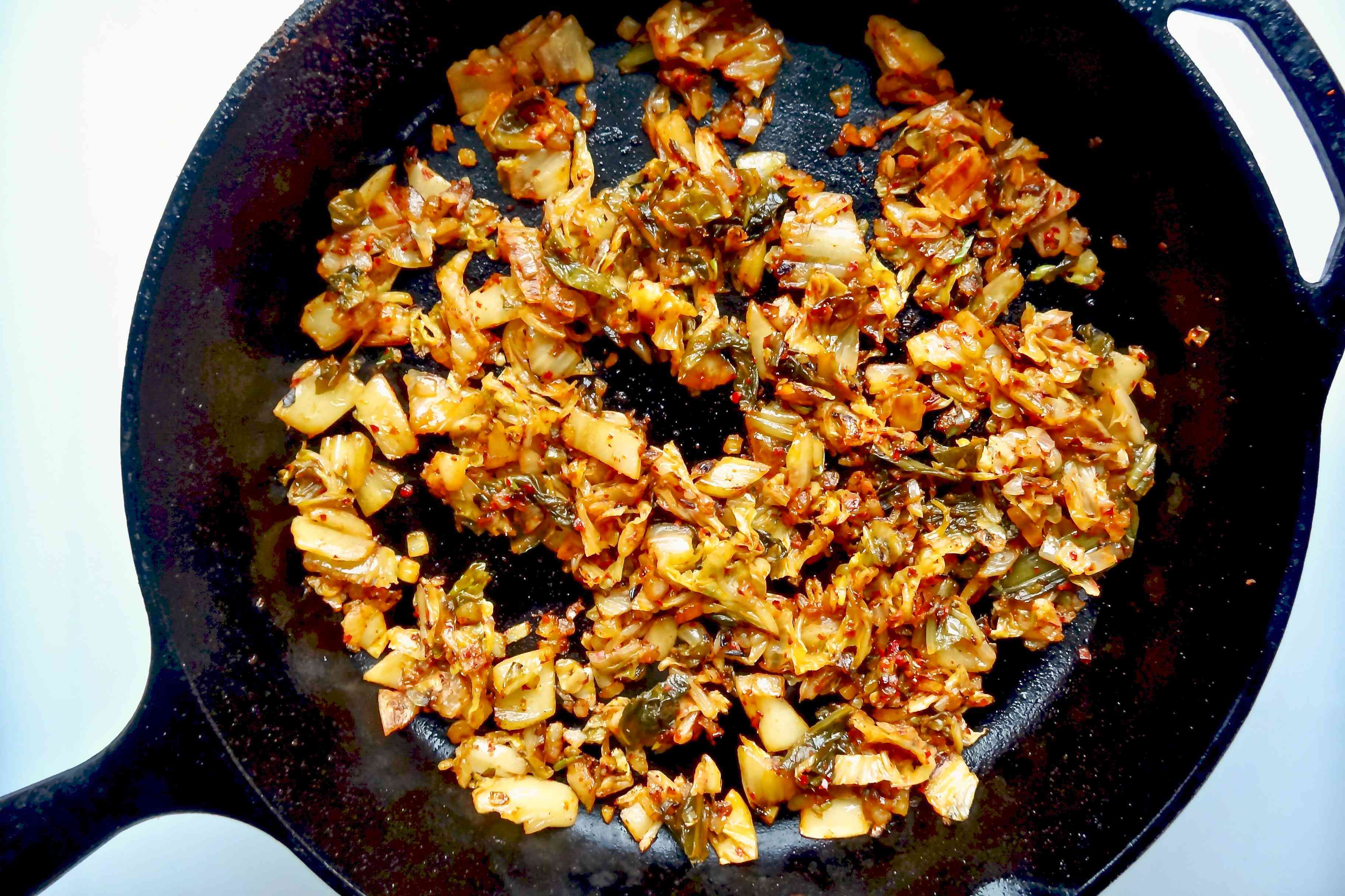 Cooking kimchi and aromatics in a skillet to make a kimchi fried rice bowl.