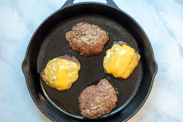 Four burgers in a cast iron skillet