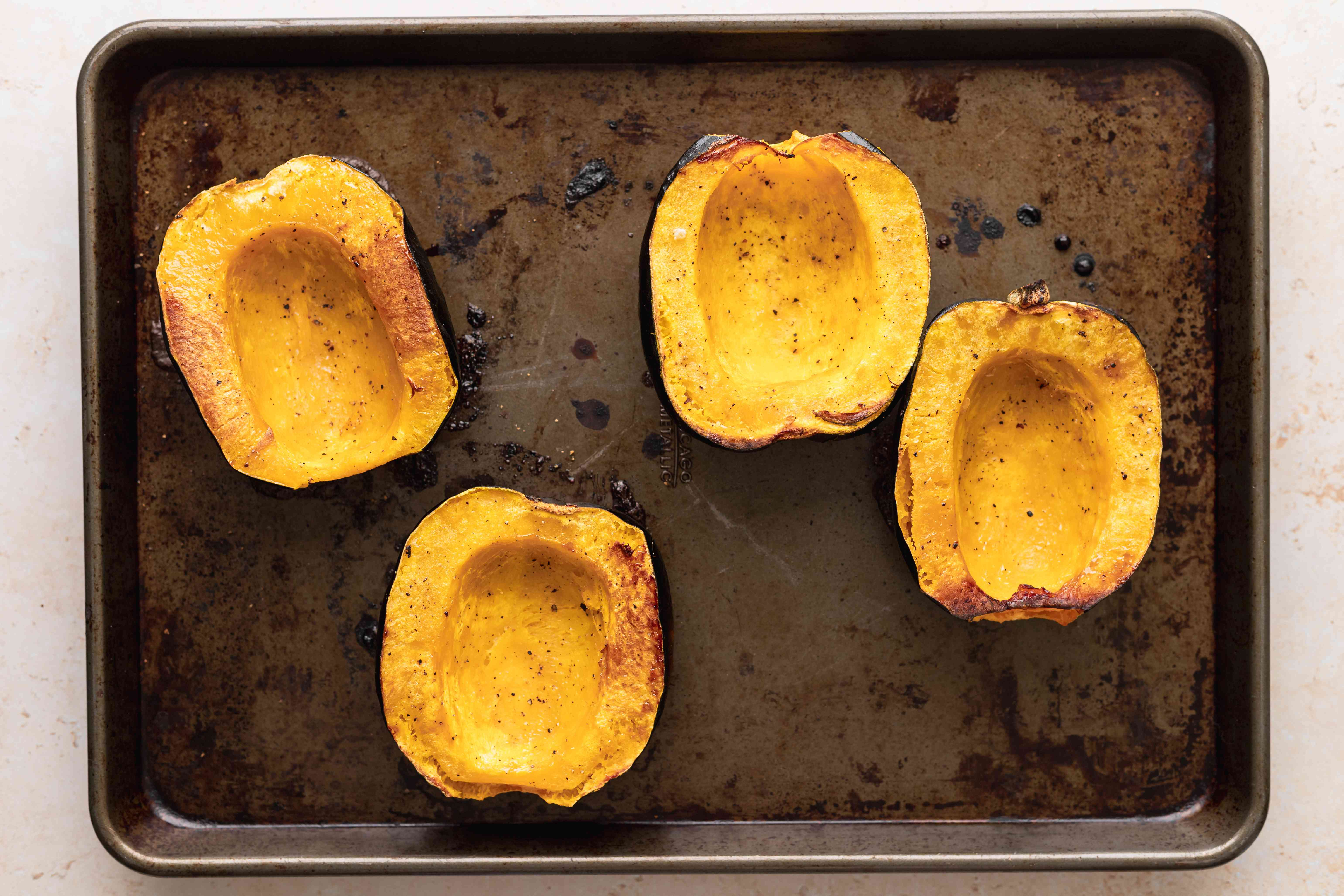 Halved acorn squash roasting on a baking sheet to make vegetarian stuffed squash.
