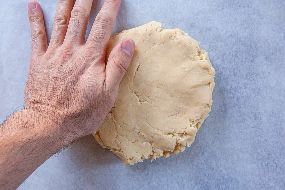 Hand presses dough dough to make the Best Sugar Cookies.