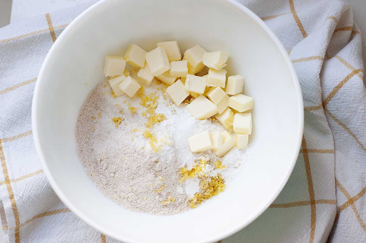 A white bowl with cubed butter, flour and lemon zest to make light strawberry shortcake. The bowl is on a yellow striped linen.